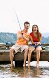 Paar dat op pijler vist Stock Foto's