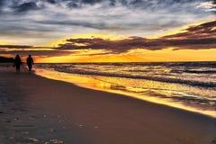 Paar dat op strand bij zonsondergang loopt Stock Foto