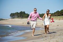 Paar dat op strand door overzees loopt royalty-vrije stock afbeeldingen