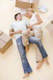 Paar dat op vloer door open dozen in nieuw huis ligt Royalty-vrije Stock Afbeelding