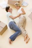 Paar dat op vloer door open dozen in nieuw huis ligt Stock Afbeeldingen