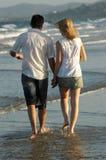 Paar dat op waterenrand bij strand loopt stock foto's