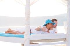Paar dat op wit bed bij het overzees ligt Royalty-vrije Stock Afbeeldingen