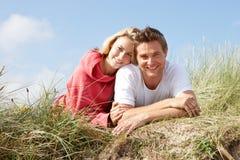 Paar dat op zandduinen legt Royalty-vrije Stock Foto's