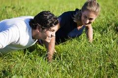 Paar dat opdrukoefeningen in de zomergras doet Stock Foto's