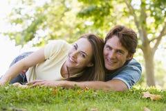Paar dat in openlucht glimlachend ligt royalty-vrije stock afbeeldingen