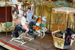 Paar dat pret op een vrolijk-gaan-ronde heeft Stock Fotografie