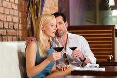 Paar dat rode wijn in restaurant drinkt Stock Foto's