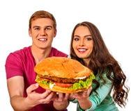 Paar dat snel voedsel eet De man en de vrouw behandelen hamburger Stock Afbeeldingen