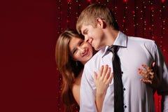 Paar dat tegen de achtergrond van lichten omhelst Stock Foto's