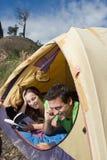 Paar dat in Tent, Lezing en het Spreken kampeert Stock Foto's