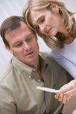 Paar dat thuis zwangerschapstest kijkt royalty-vrije stock afbeelding