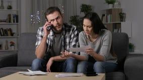 Paar dat verkeerd ontvangstbewijs op telefoon eist stock videobeelden