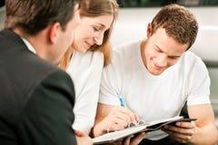 Paar dat verkoopcontract ondertekent bij autohandelaar Royalty-vrije Stock Afbeeldingen