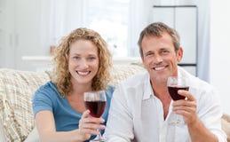 Paar dat wat rode wijn in de woonkamer drinkt Stock Fotografie