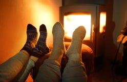 Paar dat wollen sokken draagt dichtbij open haard stock foto