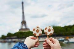 Paar in de holdingsroomijs van Parijs in vorm van voetbalbal voor de toren van Eiffel in Parijs stock afbeelding
