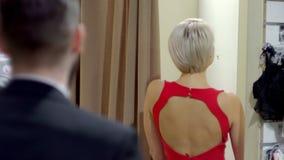 Paar in de montageruimte van de opslag van vrouwen Het meisje toont kleding aan kerel stock video