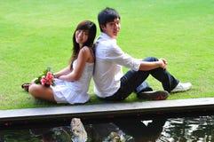 Paar in de Zitting van de liefde door de Vijver Royalty-vrije Stock Afbeelding