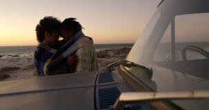 Paar in deken dichtbij pick-up bij strand tijdens zonsondergang 4k wordt verpakt die stock footage