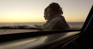 Paar in deken dichtbij pick-up bij strand tijdens zonsondergang 4k wordt verpakt die stock videobeelden