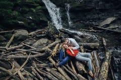 Paar dichtbij een waterval in bos royalty-vrije stock foto