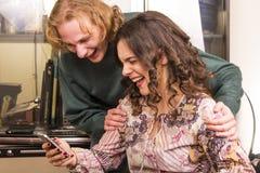 Paar die aan een bericht lachen royalty-vrije stock fotografie