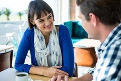 Paar die aan elkaar in koffiesho spreken stock afbeelding