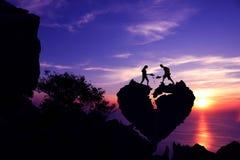 Paar die aan het scheppen van steen voor reparatie helpen de gebroken rots van de hartvorm op de berg royalty-vrije stock afbeelding