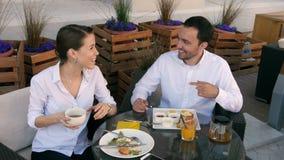 Paar die aan muziek samen in koffie op een zonnige dag in koffie luisteren stock footage