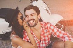 Paar die aan oor een geheim whipsering terwijl het zitten dichtbij autoped royalty-vrije stock afbeeldingen