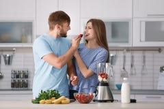 Paar die aardbeien eten terwijl het voorbereiden van heerlijke milkshake in keuken stock afbeeldingen