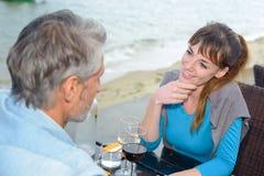 Paar die affectionately over koffielijst staren stock fotografie
