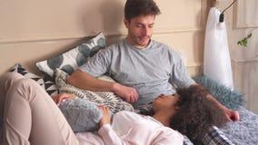 Paar die in bed bespreken stock videobeelden