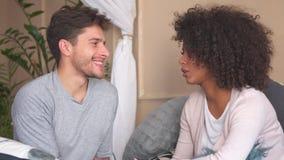 Paar die in bed bespreken stock footage