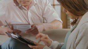 Paar die berekeningen uitvoeren die grote aankoop, schatting plannen van uitgaven stock video