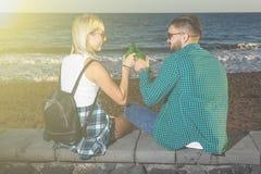 Paar die bier hebben bij kust Stock Afbeeldingen