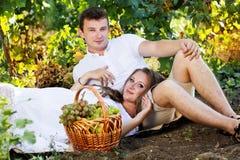 Paar die binnen - tussen rijen van wijnstokken lopen Royalty-vrije Stock Foto