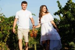 Paar die binnen - tussen rijen van wijnstokken lopen Royalty-vrije Stock Afbeelding