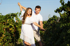 Paar die binnen - tussen rijen van wijnstokken lopen Royalty-vrije Stock Foto's