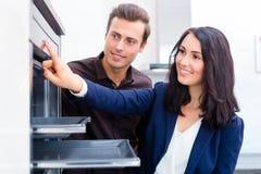 Paar die binnenlandse keuken in meubilairopslag kopen Stock Afbeeldingen