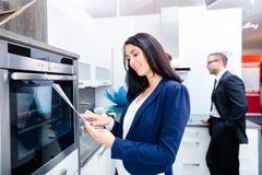 Paar die binnenlandse keuken in meubilairopslag kopen Royalty-vrije Stock Afbeelding