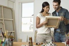 Paar die in Canvases in Kunstenaar Studio bekijken royalty-vrije stock fotografie