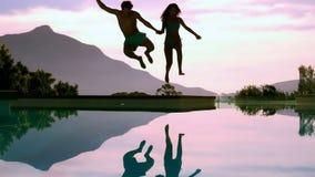 Paar die in de handen van de zwembadholding springen stock videobeelden
