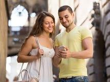 Paar die de kaart gebruiken bij smartphone Royalty-vrije Stock Foto's