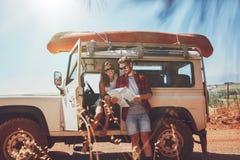 Paar die de kaart in hun auto bekijken Stock Afbeelding