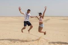 Paar die in de lucht in Sahara Desert, Tunesië, Afrika springen royalty-vrije stock afbeeldingen