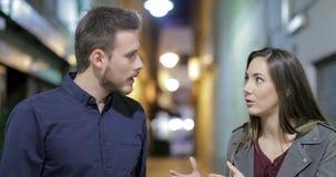 Paar die in de nacht in de straat debatteren stock videobeelden