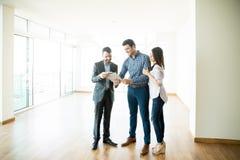 Paar die de Overeenkomst van de Verkoopaankoop door Makelaar In New Home ondertekenen stock foto's