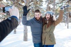 Paar die in de winterpark fotograferen Stock Afbeelding